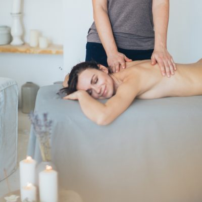 happy-client-resting-on-couch-while-receiving-massage-3865798